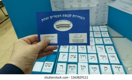 HOLON, ISRAEL. April 9, 2019. Hand of a person holding a ballot paper with an electoral envelope with ballots of different political parties. Parliamentary elections in Israel 2019. Knesset elections