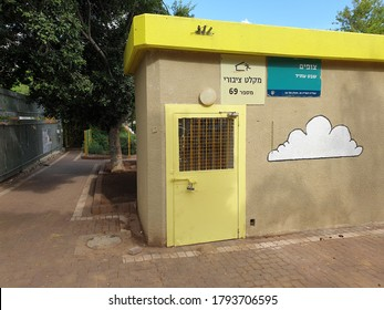 HOLON, ISRAEL. August 3, 2020. Fortified door and stairs of a public bomb and rocket shelter building by a children playground and public school in Israel. Sign in Hebrew says: public bomb shelter