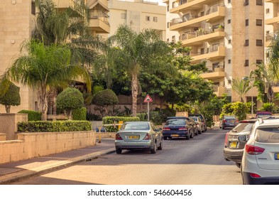 Holon, Israel-July 21, 2016:  Little quiet Yigael Yadin Street is flooded with morning sunlight. There are modern residential apartment buildings, green palm trees, parked cars along sidewalk