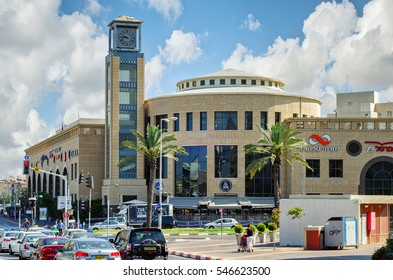 Holon, Israel-July 21, 2016:  Holon shopping mall, outdoor view of semi-round main entrance with tall tower clock. There are cars waiting traffic light. Bright sunny day on blue sky background