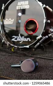 Holovanivsk, Ukraine - 09.27.2015: Shure Beta 52a microphone head lying on stage floor with Zildjian bass drum in background before concert, Rock Music concert