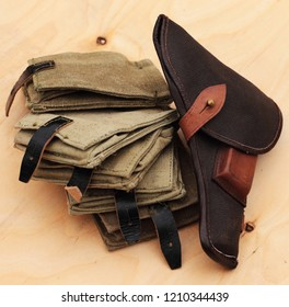 Holster from the army gun Tokarev and canvas pouches for grenades on a sheet of birch plywood