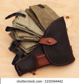 Holster from the army gun Tokarev and canvas pouches for grenades on a sheet of birch plywood.