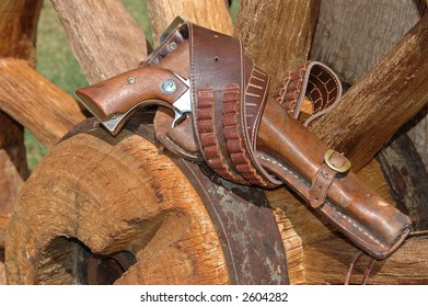 A holstered pistol on a wagon wheel