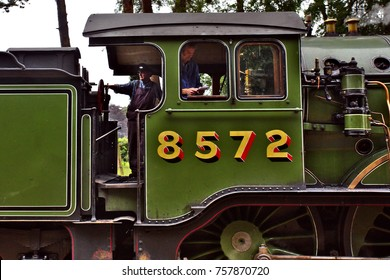HOLT, NORFOLK, ENGLAND - AUGUST 9, 2017: Driver and fireman working in a restored locomotive on the North Norfolk railway line.