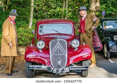 Holt, Norfolk, UK – September 14 2019. Two old men dressed in 1940s style clothing beside a vintage Austin car at the annual forties weekend in Holt Norfolk
