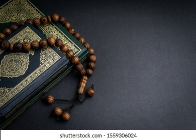 Holy Al Quran with written arabic calligraphy meaning of Al Quran and rosary beads or tasbih on black background. Copy space and crop fragment