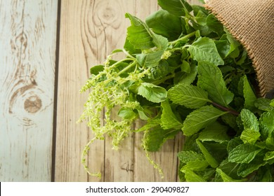 Holy basil, Sacred Basil (Ocimum sanctum) with Pepper mint leaves on old wood background