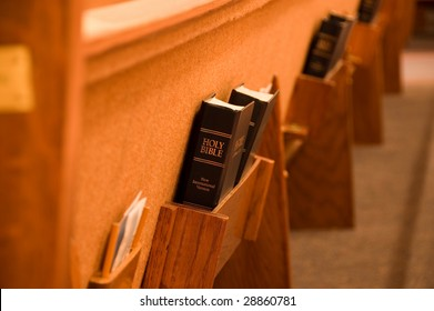 Holy Bible being held in a shelf on the back of a pew in a church