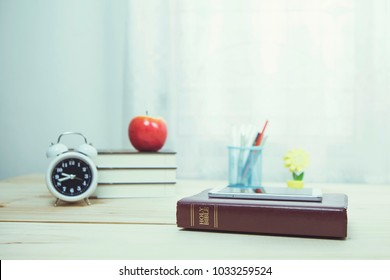 the holy bible bookwith smartphone, alarm clock, stack of books, apple and some accessory on wooden table with window light