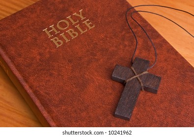 The Holy Bible, closed on a table, with a wooden cross on it. Perfect for use with any religious theme.