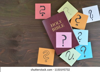 Holy bible and colorful note pads with question marks on brown wooden background as symbol for answers you can find in the bible or passages you don't understand