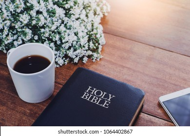Holy bible with a cup of coffee, mobile phone and flowers on wooden table against window light, Christian background with copy space