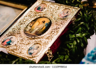 Holy Bible decorated with gold and icons, Wedding crowns stand on the table in church. Close up. Divine Liturgy.