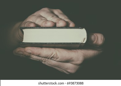 Holy Bible in man`s hands closeup. Low key image.