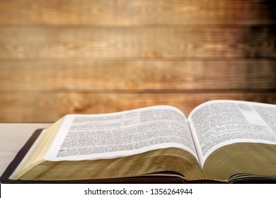 Holy bible with note book and pencil on wooden table against morning  sun light for christian devotion, copy space