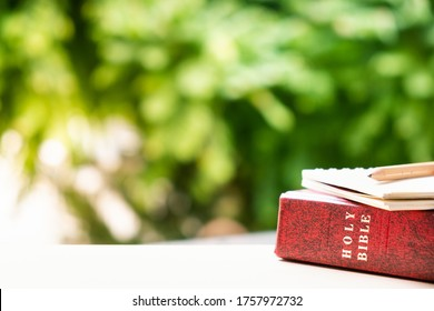 Holy Bible, notebook, and pencil with natural background