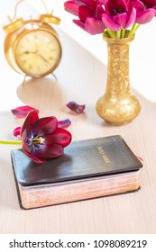Holy Bible and old gold alarm clock with flowers on wooden table background. Focus on flower over bible.