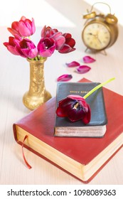 Holy Bible and old gold alarm clock with flowers on wooden table background.
