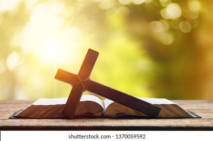 Holy Bible on the background of the Christian cross and the life-giving divine light. The hope of mankind for salvation. The way to God through prayer. The Resurrection and Rapture of Jesus.