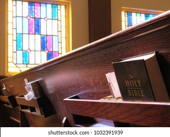 Holy Bible on church pew with stained glass background.