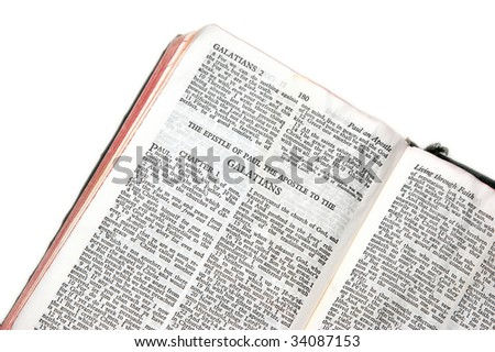 holy bible open to the epistle of paul the apostle to the galatians, against a white background