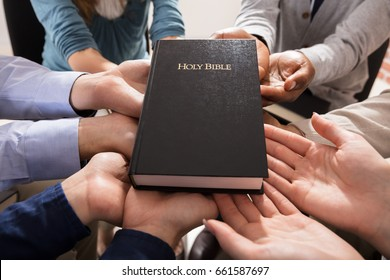 Holy Bible Over The Hands Of Diverse People