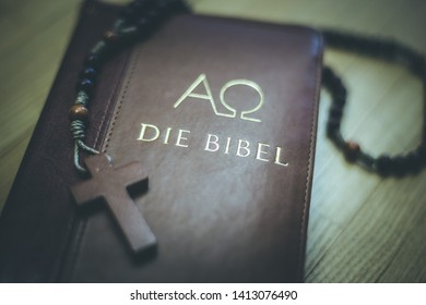"Holy bible and rosary are lying on a wooden desk, ""Die Bibel"""