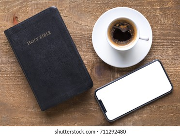 Holy Bible and smartphone with black coffee cup on wooden background. Time for study concept.