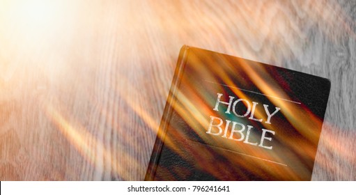 The Holy Bible and Holy spirit on fire come wooden background.Holy spirit and read bible and anointing concept.