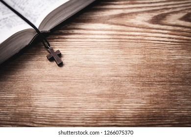 Holy Bible with wooden cross on wooden table.