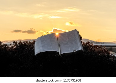 The Holy Bible (Word of God) opened during a glorious golden sunset. Sun in the center of the Bible. Background with clouds and Bright sun and intense orange and gold color. Horizontal shot.
