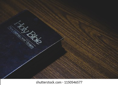 "The Holy Bible "" The Words of God""on The wooden table.Low Key Tone."