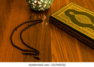 holy book for Muslims and rosary   with blue candle on the wooden background for Islamic,Friday and Eid  concept.