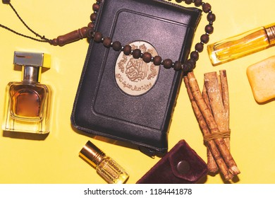 holy book of muslims and rosary, siwak, perfume on yellow background