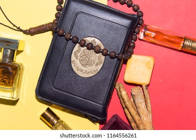 holy book of muslims and rosary,siwak, perfume on pink background