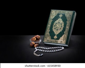 Holy Book of Quran With Rosary and Dates Over Black Background