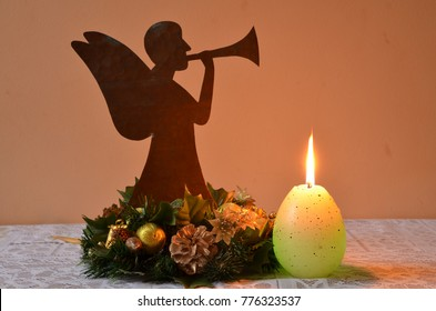 Holy Christmas crown with a trumpet Angel and burning candle