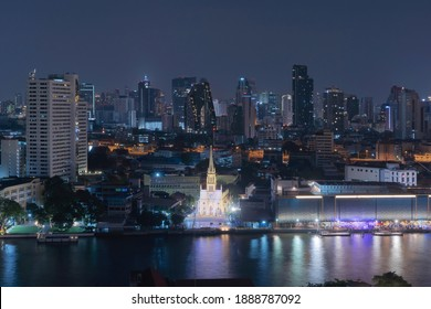 Holy church with Chao Phraya River. Thailand. Financial district and business centers in smart urban city in Asia. Skyscraper and high-rise buildings at night.
