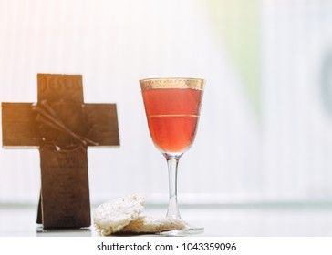 Holy communion in church.Taking Communion.Cup of glass with red wine and unleavened Bread Chalice and Cross on wooden table.The Feast of Corpus Christi Concept.