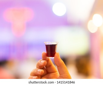Holy communion in church.Taking holy Communion.Cup of glass with red wine, bread.The Feast of Corpus Christi Concept.