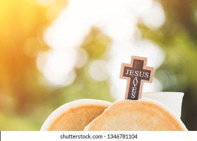 Holy communion and Jesus my savior concept.Taking Communion.Jesus saves word on Cross with Bread and Cup of glass.The Feast of Corpus Christi Concept.Christians symbols concept.