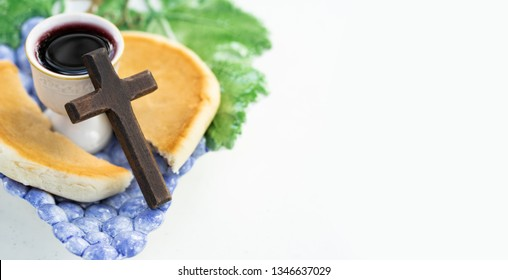 Holy communion on white marble table in church.Taking Communion.Wooden Cross with Cup of glass with red wine, bread on white table.The Feast of Corpus Christi Concept.Christians symbols concept.
