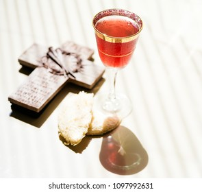 Holy communion on wooden table on church.Taking Communion.Cup of glass with red wine, bread and Holy Bible and Cross.The Feast of Corpus Christi Concept.