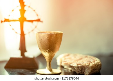 Holy communion on wooden table on church.Taking holy Communion.Cup of glass with red wine, bread.The Feast of Corpus Christi Concept.