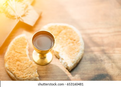 holy communion on wooden table on church.Taking Communion.Cup of glass with red wine, bread and Holy Bible and Cross on wooden table.black and white.