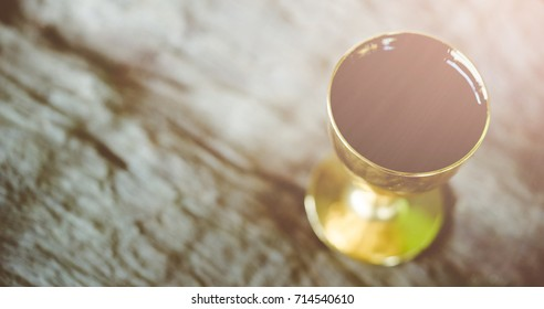 Holy communion on wooden table in church.Taking Communion.Cup of glass with red wine on wooden table.The Feast of Corpus Christi Concept.Christians symbols concept.