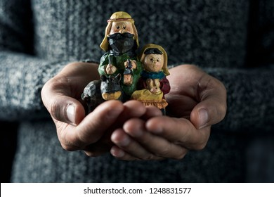 the holy family, the child jesus, the virgin mary and saint joseph, in the hands of a young caucasian man