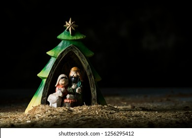 the holy family, the child jesus, the virgin mary and saint joseph, in a rustic nativity scene against a dark background with some blank space on the right