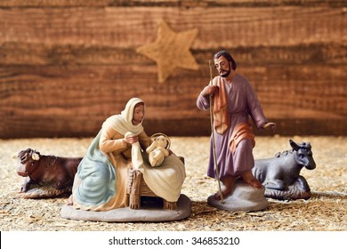 the holy family, Child Jesus, the Virgin Mary and Saint Joseph, and the donkey and the ox in a rustic nativity scene, with the star in the background